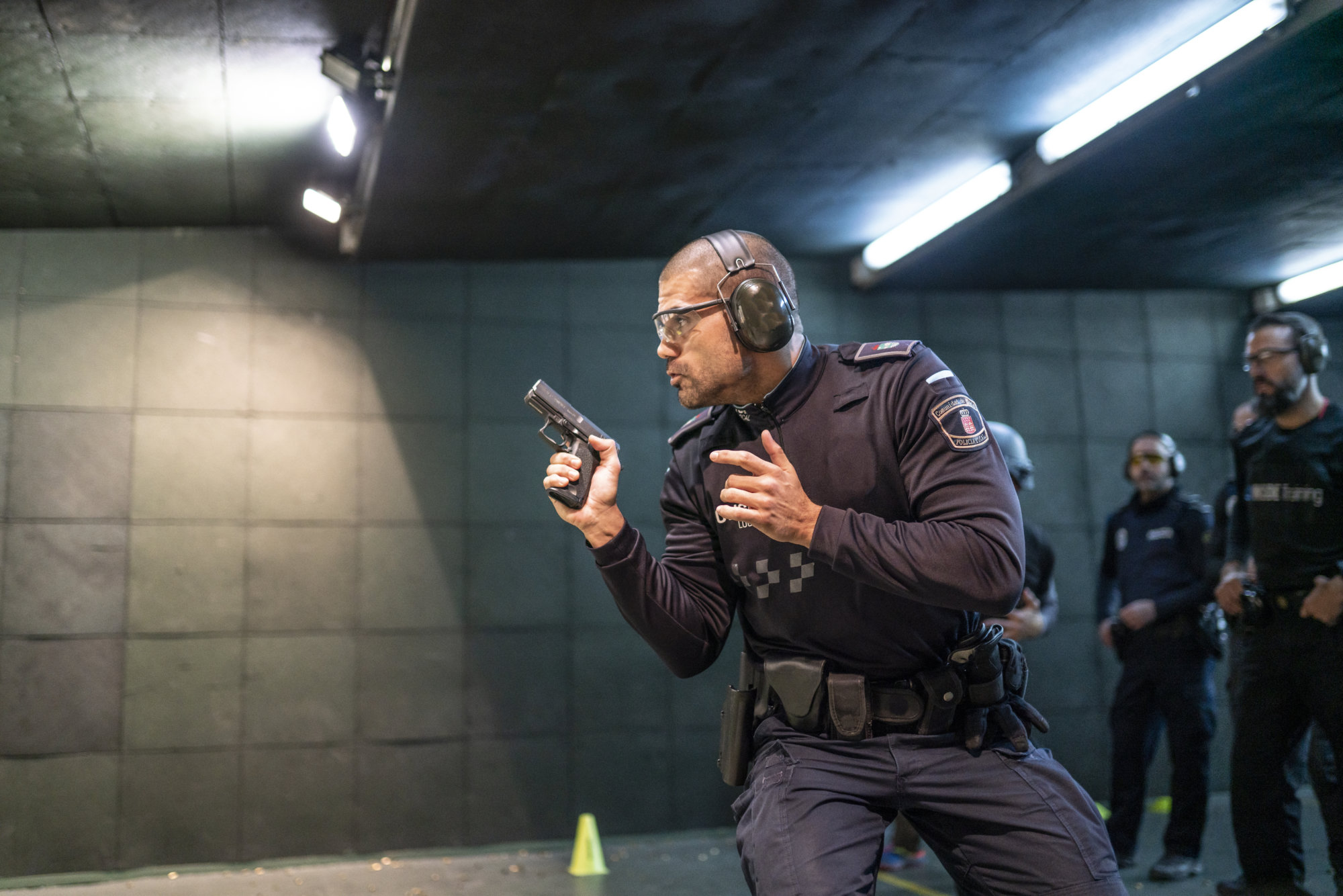 Police training in shooting gallery with short weapon.