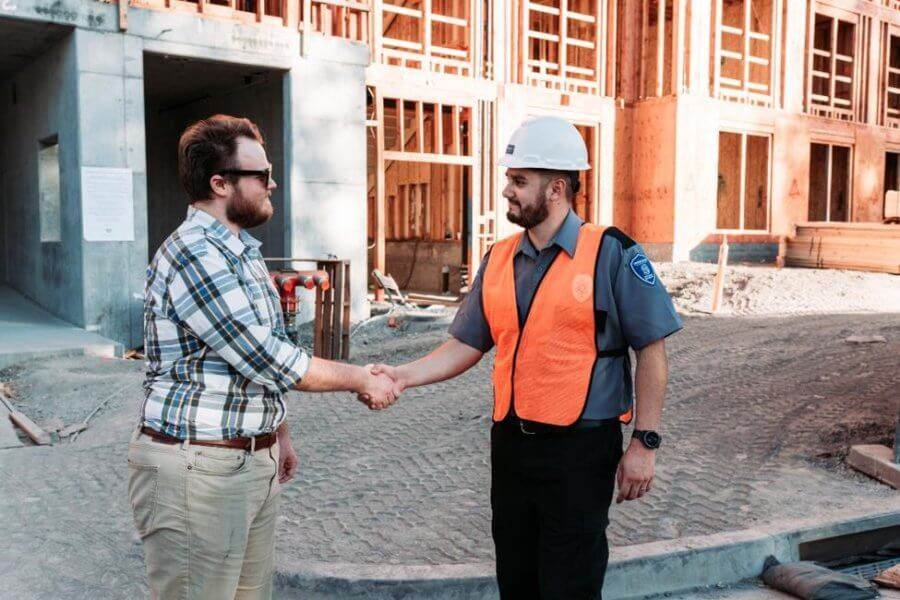 A security guard greeting a contractor at a work site